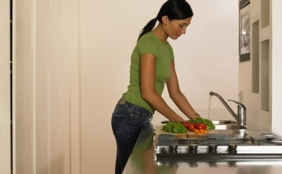 אישה שוטפת ירקות במטבח - תמונת כתבה