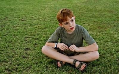 ילד יושב על דשא - תמונת כתבה