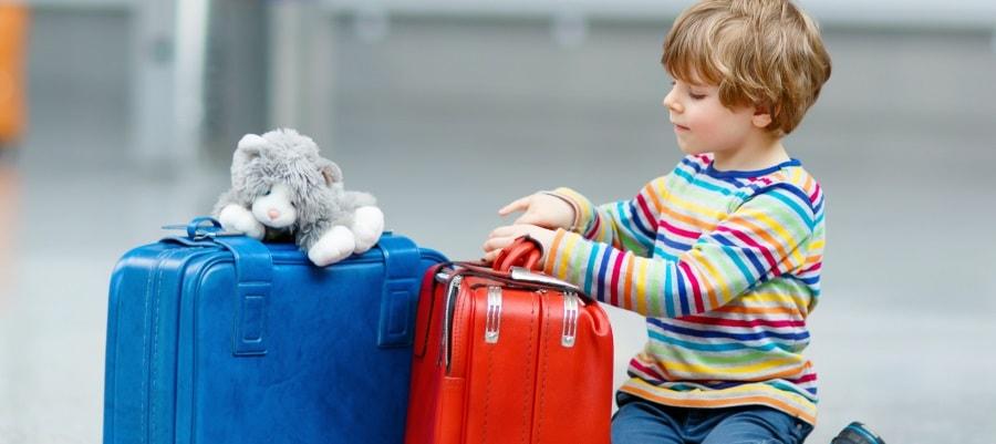 הילד עצוב וממתין עם המזוודות - יאלץ להפרד מאחד מהוריו